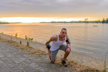 Young fitness man runner stretching legs before running