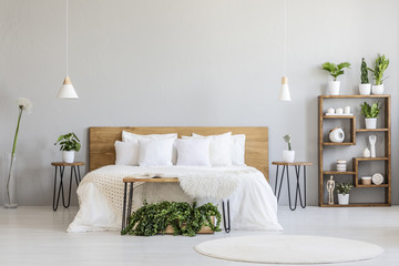 White pillows on wooden bed in minimal bedroom interior with plants and round rug. Real photo
