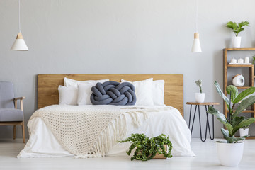 Blue knot pillow on bed with wooden headboard in grey bedroom interior with plants. Real photo