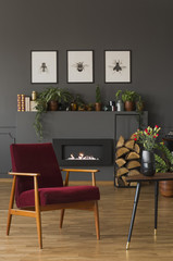 Red wooden armchair next to table in grey flat interior with posters above fireplace. Real photo