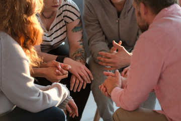 Close-up of a support group and their hands during a therapy