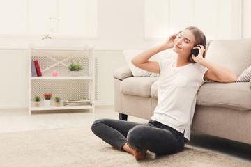 Happy young woman in headphones on floor