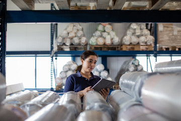 Female working in distribution warehouse with digital tablet