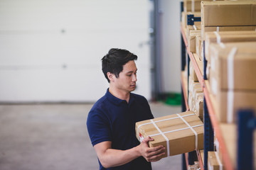 Male picking up box from shelf in distribution warehouse