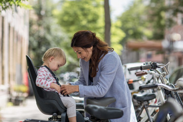 Mother putting child in bicycle seat