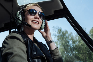 Upbeat mood. Beautiful helicopter pilot smiling cheerfully while listening to air traffic controller in her headphones Wall mural