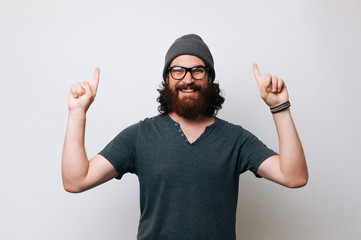 Cheerful young bearded man wearing a T-shirt and glasses and a fur hat cap. Man pointing with hands and index fingers upwards. Offer concept.