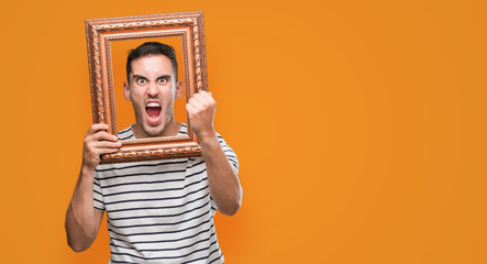 Handsome young man looking through vintage art frame annoyed and frustrated shouting with anger, crazy and yelling with raised hand, anger concept