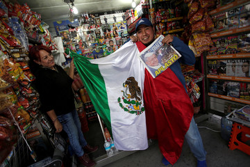People pose for a picture with a Mexican flag and a newspaper after the election of Andres Manuel Lopez Obrador as new Mexican President in Mexico City