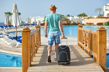 Man tourist in summer clothes with a suitcase in his hand, looking at the sea on the beach, pool in hotel, concept of time to travel