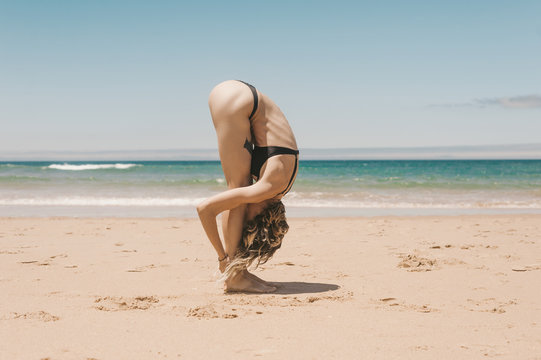 side view of young woman standing in forward fold yoga pose on sandy beach