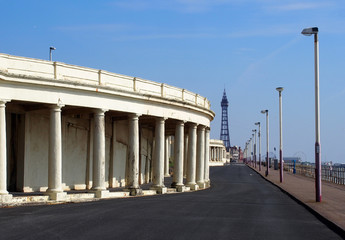 view along the promenade at blackpool showing the pedestrian walkway with old seafront shelters looking towards the pleasure beach and town centre with the tower visible