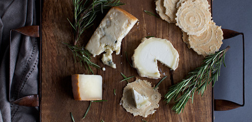 Different Cheeses on a Board with Rosemary