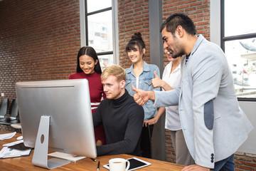 Male designer working with team for design concept at modern office. Team assist male designer to design together.