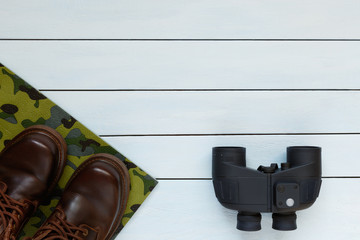 Binoculars and male shoes on a wooden background.