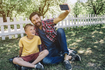 Man is sitting with his so on grass and holding phone in hand. He is taking selfie with kid. They are miling and posing on camera.
