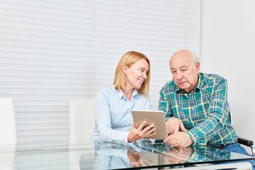 Wall Mural - Frau erklärt altem Senior einen Tablet Computer