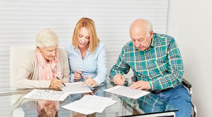 Senioren und junge Frau lösen zusammen Rätsel