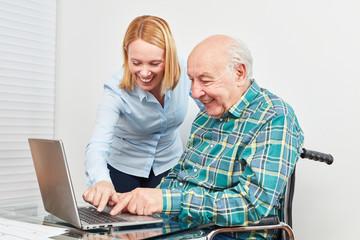 Wall Mural - Junge Frau hilft Senior am Laptop Computer