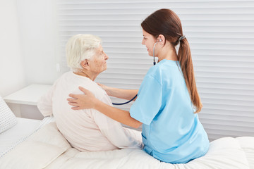 Wall Mural - Pflegehilfe mit Stethoskop untersucht Seniorin