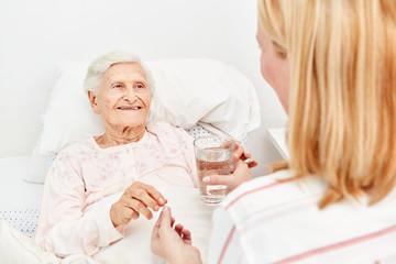 Seniorin nimmt ein Medikament mit Wasser ein