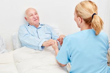 Krankenschwester hält Hände von einem Senior
