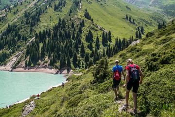 Tourist group in the mountains near Turquoise mountain lake.  Trees,  rocks around the mountain river.  Kyrgyzstan.
