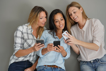 Girls on grey background using smartphone