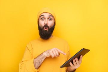 Expressive guy pointing at tablet Fotoväggar