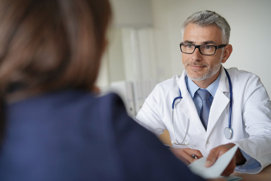 Doctor giving medical prescription to patient