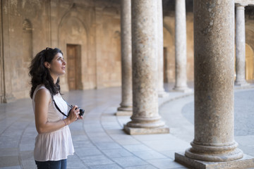 Tourist woman taking pictures to La Alhambra in sunny day. Carlos V palace