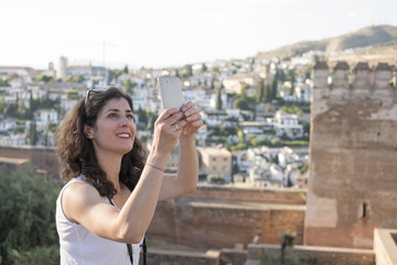 Tourist woman taking pictures to La Alhambra in sunny day. Selfie with smartphone