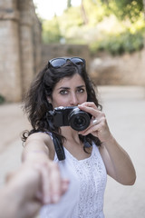 Tourist woman taking pictures to La Alhambra in sunny day.