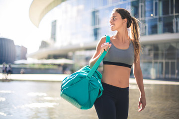 Sportive girl waking in the city wearing fitness clothes