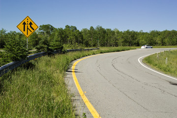 Traffic merge sign beside rural highway
