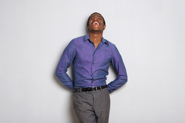 cheerful young african businessman laughing and looking up