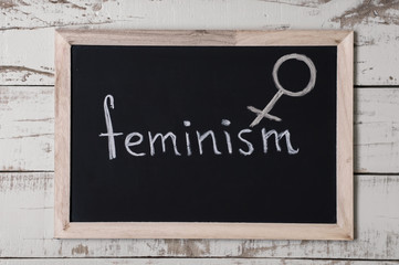 "The word ""feminism"" and venus symbol at blackboard, top view"
