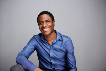 handsome young african american businessman smiling against gray wall