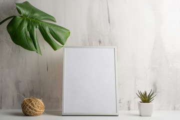 Empty white frame with flower on wall background. The concept of design and font inscriptions and image placement
