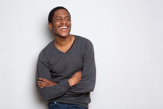 confident african american man smiling with arms crossed against white background
