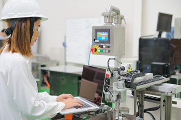 Woman software engineers developing automated robotic in production line, Industry
