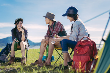 Asian group friends travel camping together in forest with backpack and tent picnic drinks beer,water at nature outdoor young teenager talking relax,rest near mountain view.