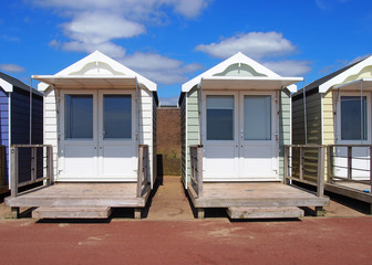 traditional wooden beach huts painted in bright colours in bright summer sunshine with blue sky and white clouds