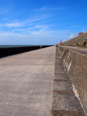 the long concrete pedestrian walkway along the seawall in blackpool lancashire with summer sunshine and sea