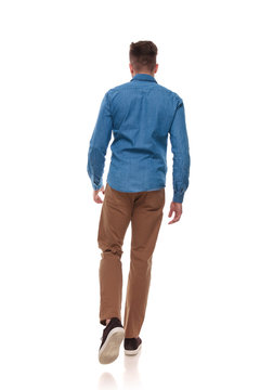 back view of young man in casual clothes walking