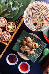 Fried chicken wings in Thai northeastern style with garlic and kaffir lime leaves served on banana leaf.