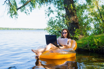 Business woman working on a laptop in an inflatable ring on the river, the concept of working on vacation.