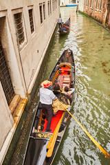 Venetian gondolier punting gondola through canal in Venice, Italy