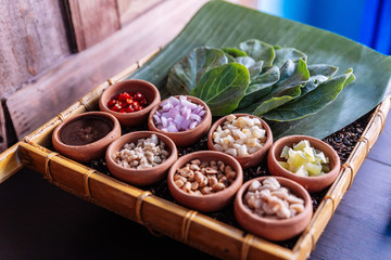 "Thai appetizer called ""Miang Kham"", some of nutritious snack wrapped in leaves with a sweet and salty sauce."