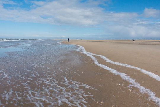 Nordsee endloser Strand mit Wellen und Spaziergängern